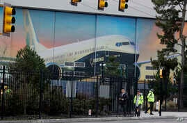 FILE - Workers exit the Boeing factory in Renton, Washington, where the company's 737 Max airplanes are built, with a painted exterior door of the factory in the background, Dec. 17, 2019.