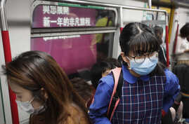 Commuters wear protection masks inside a subway train in Hong Kong, Jan. 7, 2020.