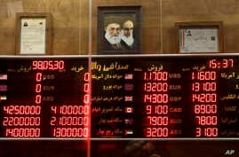FILE - Various rates and prices for currencies and gold coins are displayed at an exchange bureau, in Tehran, Iran, Aug. 21, 2019.