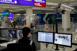 FILE - An officer monitors passengers arriving at Hong Kong International airport in Hong Kong, Jan. 4, 2020.