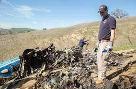 In this image taken Jan. 27, 2020, and provided by the National Transportation Safety Board, NTSB investigators Adam Huray, right, and Carol Hogan examine wreckage as part of the investigation of a helicopter crash near Calabasas, California.