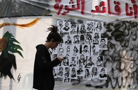 """FILE - An anti-government protester checks his mobile phone in front of a wall of graffiti in Arabic that reads, """"I am the revolution leader,"""" in downtown Beirut, Lebanon, Nov. 21, 2019."""