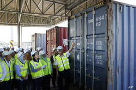 Malaysia's Environment Minister Yeo Bee Yin, third from left, inspects a container with plastic waste at a port in Butterworth, Jan. 20, 2020.