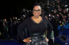 FILE - Oprah Winfrey poses for photographers upon arrival at a film premiere in London, Britain, March 13, 2018.