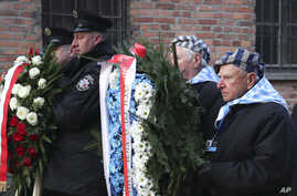 Survivors carry a wreath at the Auschwitz Nazi death camp in Oswiecim, Poland, Jan. 27, 2020.