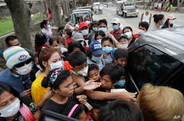 Residents scramble to obtain relief supplies being distributed at a town near Taal volcano, in Tagaytay, Cavite province, Philippines, Jan.19, 2020.