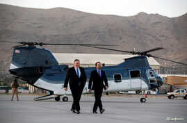 FILE - Secretary of State Mike Pompeo walks from a helicopter with U.S. Ambassador to Afghanistan John Bass, as Pompeo returns to his plane after an unannounced visit to Kabul, Afghanistan, June 25, 2019.