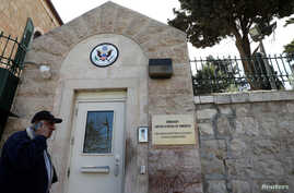 "FILE - A man walks past a wall with plaques bearing the words ""Embassy United States of America"" at the premises of the former U.S. Consulate in Jerusalem, March 12, 2019."