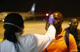 FILE - A health worker checks the temperature of a man arriving at Bata Airport, in Litoral, Equatorial Guinea, Jan. 14, 2015.
