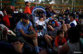 Migrants, part of a caravan travelling to the U.S., gather near the border between Guatemala and Mexico, in Tecun Uman, Guatemala, Jan. 20, 2020.