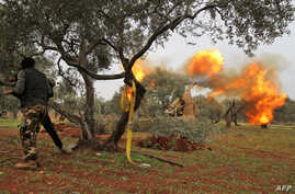 """Members of Syria's opposition """"National Liberation Front"""" fire heavy artillery guns at government forces in the village of…"""