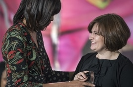 Former US First Lady Michelle Obama (L) presents Elena Milashina of Russia with the Secretary of State's International Women of Courage Award inside the Dean Acheson Auditorium of the US Department of State March 8, 2013, in Washington.