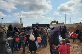 The gate to Manbij, Syria where displaced families wait to enter, seeking relative safety hundreds of kilometers from Idlib, pictured on Feb. 21, 2020. (H.Murdock/VOA)