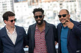 Producer Christophe Barral, from left, director Ladj Ly and producer Toufik Ayadi pose for photographers