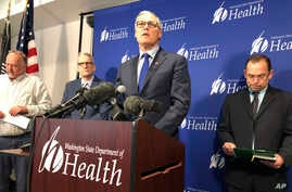 Washington Gov. Jay Inslee, center, speaks Tuesday Jan. 21, 2020, at a news conference in Shoreline, Wash.