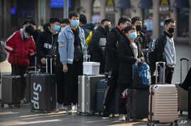 Travelers wear face maTravelers wear face masks as they stand outside the Beijing Railway Station in Beijing, Jan. 31, 2020. sks as they stand outside the Beijing Railway Station in Beijing, Friday, Jan. 31, 2020. The U.S. advised…