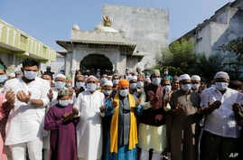 Indian Muslims wear masks and pray for the prevention of coronavirus during a special prayer after Friday prayers at a mosque in Ahmadabad, India, Jan. 31, 2020.