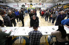Local residents check-in after arriving at an Iowa Democratic caucus at Hoover High School, Monday, Feb. 3, 2020, in Des Moines.