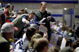Precinct 68 Iowa Caucus voters seated in the Biden section hold up their first votes as they of the caucus as they are counted…