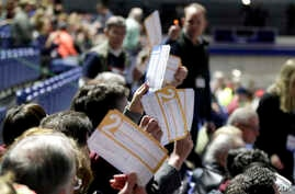Caucus goers seated in the section for Democratic presidential candidate former Vice President Joe Biden hold up their votes