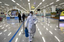 State Commission of Quality Management staff member in protective gear carries a disinfectant pray can as they continue to check the health of travelers and inspect and quarantine goods at the Pyongyang Airport in Pyongyang, North Korea, Feb. 1, 2020.