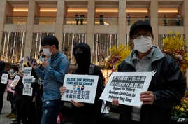 "Protesters wearing masks hold placards reads"" Close the border, say no to China"" during a protest at a mall in Hong Kong,…"
