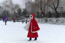 A girl wears a face mask as she walks across a frozen canal during a snowfall in Beijing, Feb. 5, 2020. The little-understood new coronavirus has killed nearly 500 people in mainland China, but it has also spread panic and discrimination around the world.
