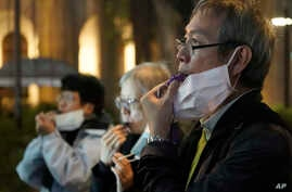 People with masks, blow whistles to representing whistleblower during a vigil for Chinese doctor Li Wenliang, in Hong Kong,…