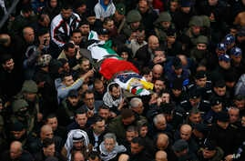 Palestinians carry the body of policeman Tariq Badwan during his funeral in the West Bank village of Azoun near Qalqilya, Feb. 7, 2020.