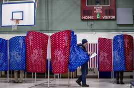 A man walks out of a voting booth during the New Hampshire Primary at Parker-Varney Elementary School, Feb. 11, 2020.