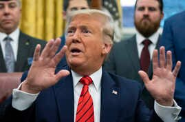 President Donald Trump speaks to reporters during the Supporting Veterans in STEM Careers Act signing ceremony in the Oval…