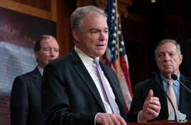 Sen. Tim Kaine, D-Va., center, joined at by Sen. Tom Udall, D-N.M., left, and Sen. Dick Durbin, D-Ill., speaks to reporters…