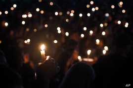 FILE - Attendees hold up their candles at a candlelight vigil for the victims of the shooting at Marjory Stoneman Douglas High School, in Parkland, Florida, Feb. 15, 2018.