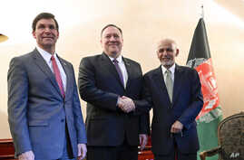 US Secretary of State Mike Pompeo, center, shakes hands with Afghan President Ashraf Ghani, right, as US Secretary of Defense…