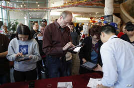 People sign in on tablet computers at an early voting location in the Chinatown Plaza, Feb. 15, 2020, in Las Vegas.