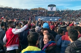 FILE - In this Nov. 23, 2019, file photo, demonstrators stage a protest on the field at the Yale Bowl disrupting the start of…
