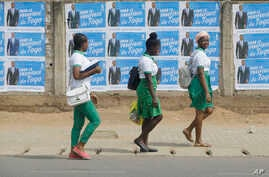 School girls walk past election posters of Togo's Incumbent President Faure Gnassingbe, Presidential Candidate of Union for the Republic, on the street in Lome, Togo, Feb. 21, 2020.