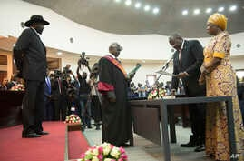 The president of South Sudan, Salva Kiir Mayardit, left, swears in Dr. Riek Machar as the first Vice President of South Sudan,…