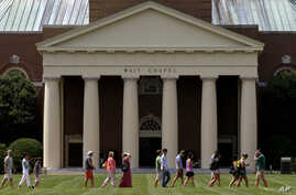 A group walks across the lawn on the campus of Wake Forest University in Winston-Salem, N.C. Wednesday, May 28, 2014 where poet…