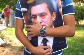 A man holds a Mubarak poster in front of Maadi Military hospital to share the celebration of the national day with Mubarak while he was hospitalized in 2015.