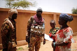 Malian Armed Forces (FAMa) soldiers speak with a woman during the Operation Barkhane in Ndaki, Mali, July 29, 2019. Picture…
