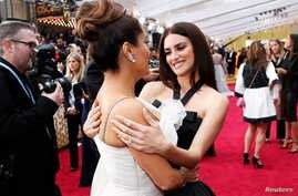 Penelope Cruz talks with Salma Hayek on the red carpet during the Oscars arrivals at the 92nd Academy Awards in Hollywood