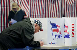 A man wearing a stars and stripes hat votes in the primary election at a polling station in Epping, New Hamphire.