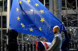 FILE PHOTO: Workers replace the British flag outside the European Parliament building with the European Union flag, in Brussels…