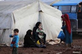 Internally displaced people sit outside tents at a makeshift camp in Azaz, Syria February 19, 2020.  REUTERS/Khalil Ashawi -…