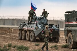 FILE - Russian troops with military vehicles are seen on patrol outside the town of Darbasiyah in Syria's northeastern Hasakeh province, on the border with Turkey, Nov. 1, 2019.