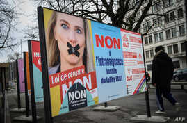 A campaign poster showing gagged Swiss MP Celine Amaudruz of right wing populist Swiss People's Party and asking voters in a referendum to reject a proposed ban on discrimination based on sexual orientation, is seen in Geneve, Switzerland, Jan. 30, 2020.