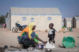 FILE - A displaced Burkinabe woman and child prepare food, in the Pissila town camp, near Kaya, Burkina Faso, Dec. 10, 2019.