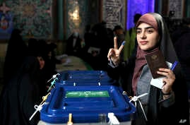 A woman flashes a victory sign with her inked finger while voting in parliamentary elections, at a polling station in Tehran, Iran, Feb. 21, 2020.