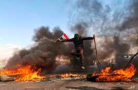n anti-government protester jumps over burning tires blocking a street during a demonstration against newly-appointed Prime Minister Mohammed Allawi, in Najaf, Iraq, Feb. 2, 2020.